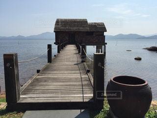 水の体の横に座っている木製のベンチの写真・画像素材[871417]