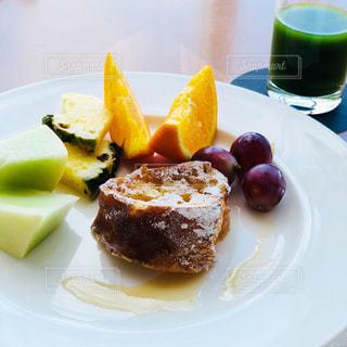 フルーツをのせた白い皿の上のケーキの一部の写真・画像素材[1129721]