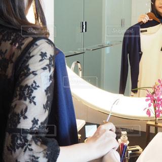 鏡の前で服を選ぶ女性の写真・画像素材[2128346]
