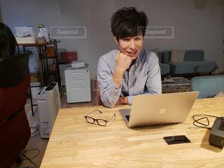 ラップトップを使用してテーブルに座る男性の写真・画像素材[1824334]