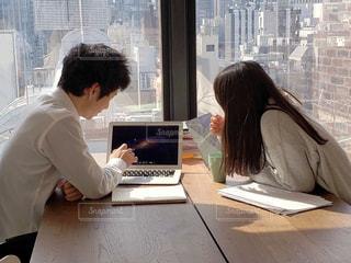 ラップトップコンピュータを使ってテーブルに座っている人の写真・画像素材[2122322]