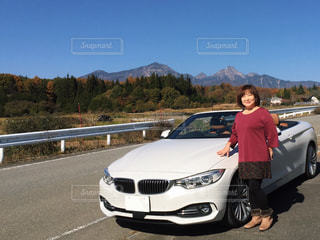 カメラに向かってポーズをとる車の後ろに乗っている男の写真・画像素材[2276604]