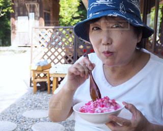 食べ物を食べるテーブルに座っている人の写真・画像素材[2388902]