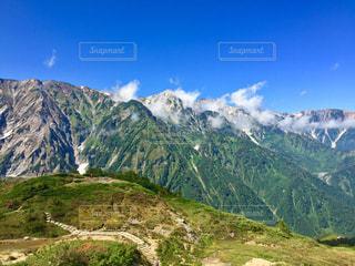 近くに木々 や背景の山と丘の中腹のアップ - No.900904
