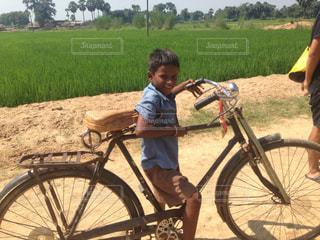 未舗装の道路を自転車に乗る男の写真・画像素材[879306]