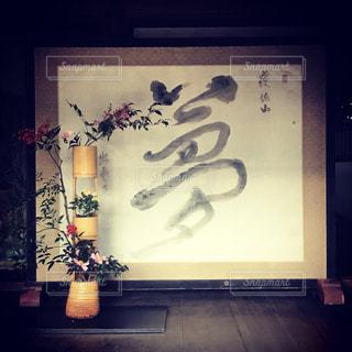 暗い部屋に座っている花の花瓶の写真・画像素材[882570]