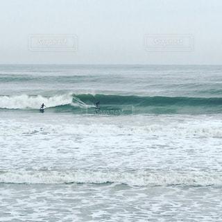 海でサーフボードで波に乗って男の写真・画像素材[876871]