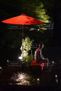 赤い傘とイスに座っている男の人の写真・画像素材[884823]