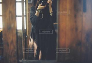 カメラにポーズ鏡の前に立っている人の写真・画像素材[1233336]