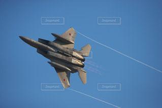 澄んだ青い空を飛んでいるジェット戦闘機の写真・画像素材[953790]