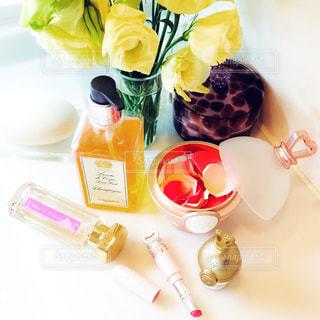 テーブルの上の花と化粧品の写真・画像素材[882989]