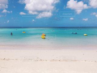 海の横にある砂浜に座っている人々 のグループの写真・画像素材[882895]