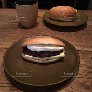 あんバターサンドとコーヒーがテーブルの上に乗ってます。の写真・画像素材[915583]