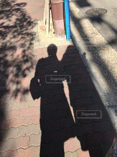 レンガ壁の前に立っている男の写真・画像素材[901910]