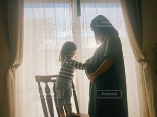 窓の前に立っている親子の写真・画像素材[2717287]