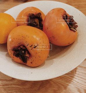 オレンジとテーブルの上のリンゴをトッピング白プレートの写真・画像素材[929892]