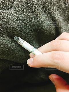 吸いかけのたばこを持っている手の写真・画像素材[1132150]