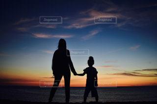 バック グラウンドで夕焼けのビーチに立っている人の写真・画像素材[894625]
