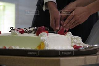 テーブルの上のケーキを切る人の写真・画像素材[892600]