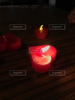 木製テーブルの上に座っている赤いロウソクの写真・画像素材[1587325]