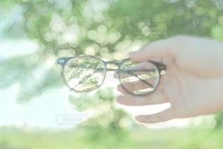 手にサングラスを持っているの写真・画像素材[1594091]