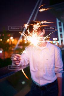 線香花火を手に持っている男性の写真・画像素材[1603933]