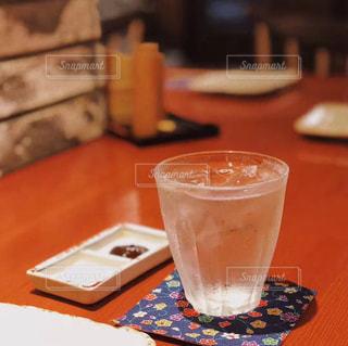 テーブルの上のコーヒー カップの横にあるオレンジ ジュースのガラスの写真・画像素材[1761680]