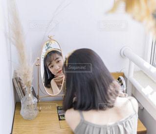 鏡の前に立っている女性がカメラのポーズをとっているの写真・画像素材[2107941]