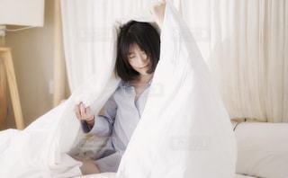 ベッドの上に座っている女性の写真・画像素材[2129741]