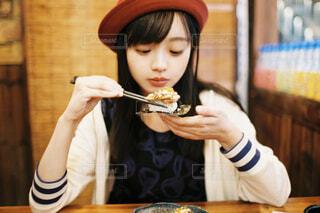 テーブルの上に座っている寿司を食べる女性の写真・画像素材[3857269]