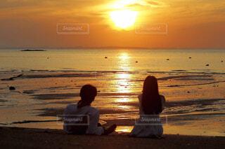 夕日の前のビーチに座っている人の写真・画像素材[3867748]