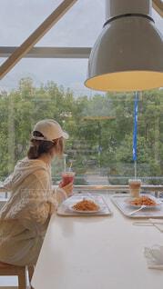 食べ物を食べるテーブルに座っている人々のグループの写真・画像素材[4133144]
