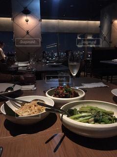 テーブルの上に食べ物と夜景の写真・画像素材[895202]