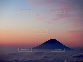 背景の山が付いている水に沈む夕日の写真・画像素材[899551]