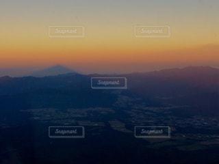 背景の山が付いている沈む夕日の写真・画像素材[900033]