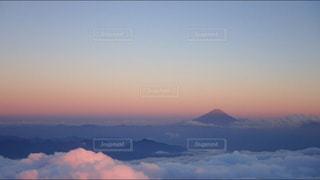 背景の山が付いている水の体に沈む夕日の写真・画像素材[900037]