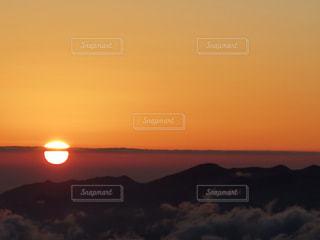 背景の山が付いている水の体に沈む夕日の写真・画像素材[901416]