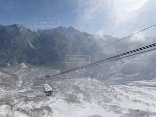 雪に覆われた山をスキーに乗る男の写真・画像素材[910968]