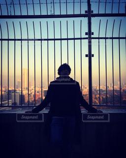 屋上で柵に寄りかかる人のシルエットの写真・画像素材[895880]