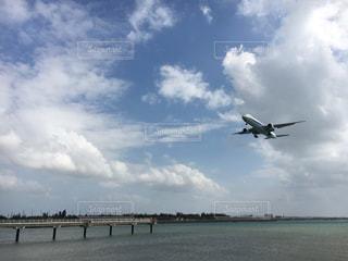 曇りの日に空を飛んでいる飛行機の写真・画像素材[896166]