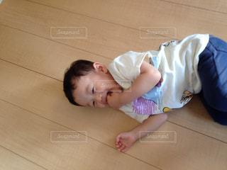 小さな男の子が床に横たわっています。の写真・画像素材[1317032]