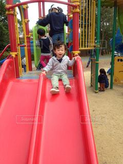 遊び場で赤いスライドの中の少年の写真・画像素材[1662739]