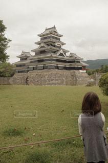 草の覆われてフィールド上に立っている人の写真・画像素材[899394]