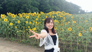 黄色の花の前に立っている女性 - No.901131