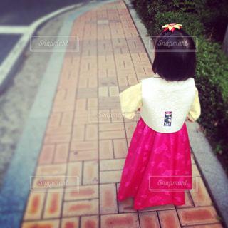 歩道の上に座っている少女の写真・画像素材[902327]