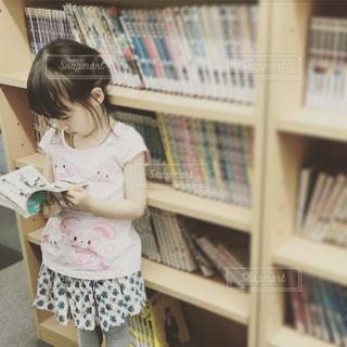 本棚の前で本を読む小さな女の子の写真・画像素材[902370]