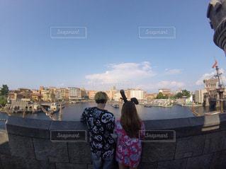 水の体の前で立っている女性の写真・画像素材[902973]
