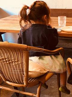 木製の椅子に座っている女の子の写真・画像素材[911107]