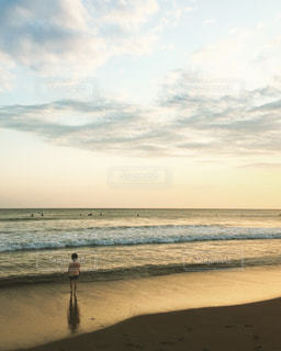 海岸の夕日と少年の写真・画像素材[905467]
