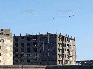 建物の上を飛んでいる鳥の写真・画像素材[905297]